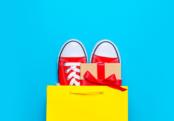 big red gumshoes and beautiful gift in cool shopping bag on the wonderful blue background