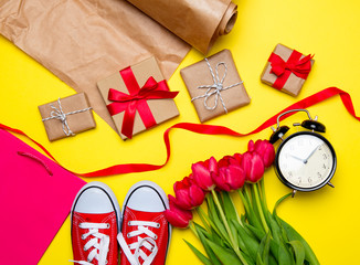 bunch of red tulips, red gumshoes, cool shopping bag, alarm clock, things for wrapping and beautiful gifts on the wonderful yellow background