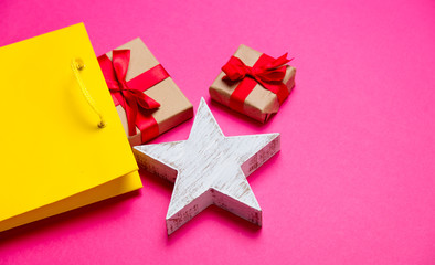 cute gifts, star shaped toy and shopping bag on the wonderful pink background