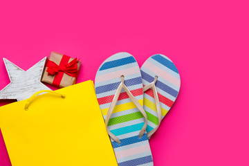 cute gift and star shaped toy in beautiful yellow shopping bag and colorful sandals on wonderful pink background