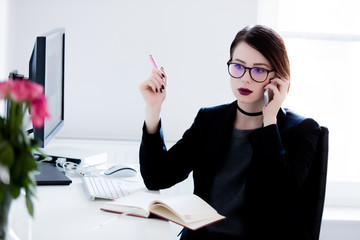 beautiful young woman sitting at the desk and talking on the phone in the cool bright office