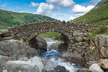 Stockley Bridge spans Grains Gill in the Lake District National Park, Cumbria. The bridge forms part of the footpath to Green Gable mountain and is a popular walking route near Seathwaite Fell.