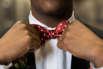 Adjusting red bowtie for prom