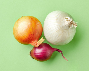 various onions on green background