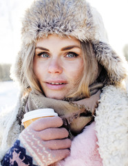 young pretty teenage hipster girl outdoor in winter snow park having fun drinking coffee, warming up happy smiling, lifestyle people concept
