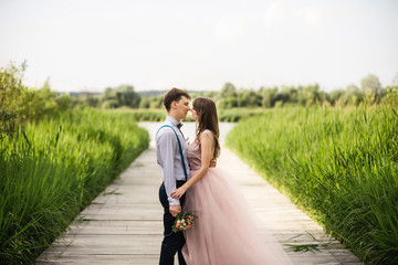 Beautiful and stylish bride and groom embracing on bridge in park. Happy wedding couple