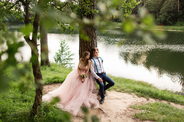 Newlyweds couple in love sitting on bench near lake. Beautiful landscape for wedding day