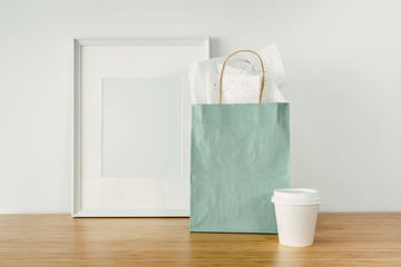 Blank mint package with handles, white cup and white photo frame with copy space for your design or logo, Mock-up of craft shopping bag, paper cup and photo frame on the wooden table.