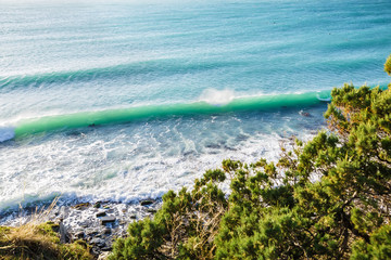 Turquoise rolling wave slamming on the rocks of the coastline