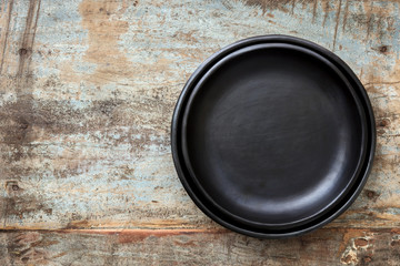 Empty Rustic Black Plates over Grunge Timber Top View