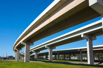 Highway overpass crossing neighborhood with a blue sky background