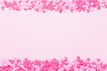 Pink and red heart sprinkles on the pink background. Flat lay, top view.  Valentines background. Romantic border