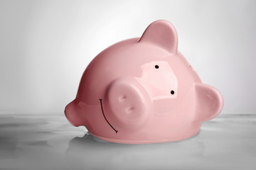 Pink piggy bank in water on light background