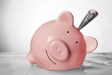 Pink piggy bank with banknote in water on light background