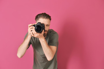 Handsome photographer on color background