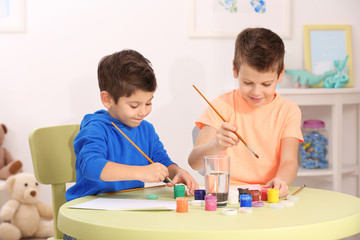 Cute little boys drawing pictures and sitting at table, closeup