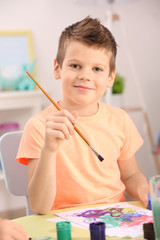 Cute little boy drawing picture and sitting at table, closeup