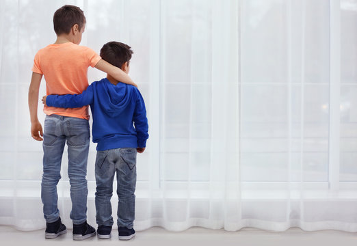 Little brothers standing together near window at home