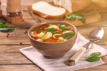Bowl with vegetable soup and spoon on napkin