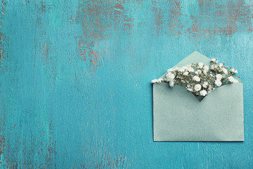 Decorative envelope with beautiful flowers on blue textured background