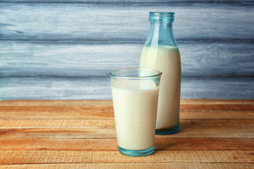 Glass of tasty milk with bottle on wooden table
