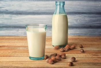 Glass of tasty hazelnut milk with bottle on wooden table