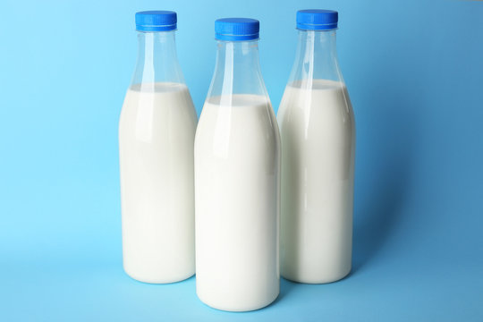Bottles of tasty milk on blue background