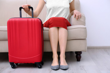 Young tourist with suitcase sitting on sofa at home