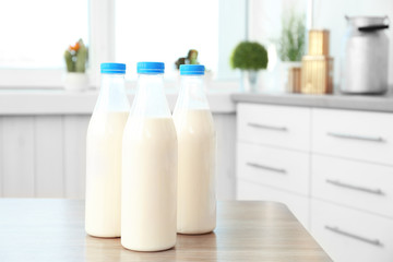 Three bottles of milk on table in kitchen