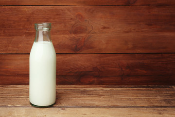 Bottle of milk on wooden background