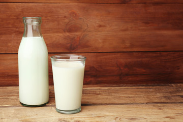 Bottle and glass of milk on wooden background