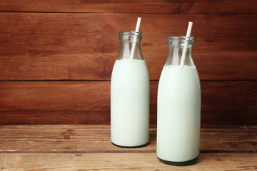 Two bottles of milk with straws on wooden background