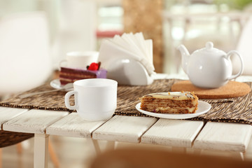 Plate with tasty cake and cup of tea on table in cafe