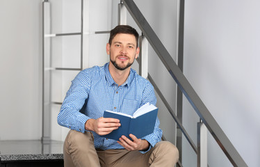 Handsome young man reading book while sitting on stairs at home