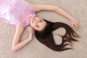Beautiful young woman with heart-shaped hair strands lying on carpet at home