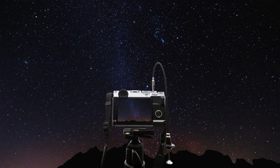 Digital camera on camera tripod taking a photo of milky way at night, with clear sky full of star