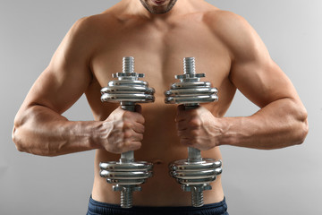 Sporty man doing exercises with dumbbells on light background, closeup