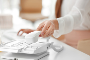 Hand of young woman picking up telephone receiver for making call in office