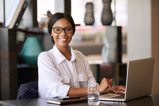 Beautiful young black woman smiling at camera while seated behind her personal computer, where she was working on managing her finances for the upcoming tax period and making online payments.