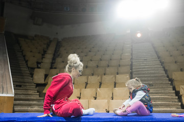 future circus artist. Female gymnast sitting with daughter of arena in circus.