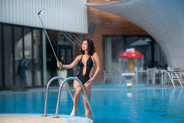Gorgeous smiling woman in a black sexy swim suit makes selfie photo with selfie stick on luxury resort with blurred background