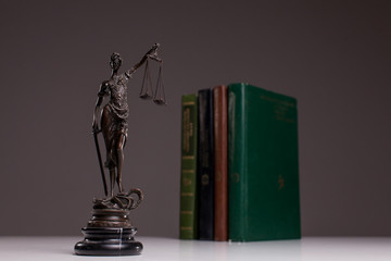 Statuette of Themis the symbol of law on old wooden floor with legal codes.