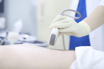 Doctor conducting ultrasound examination of abdomen to a patient