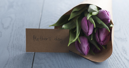 mothers day greeting card on blue table with bouquet of purple tulips on it, 4k photo