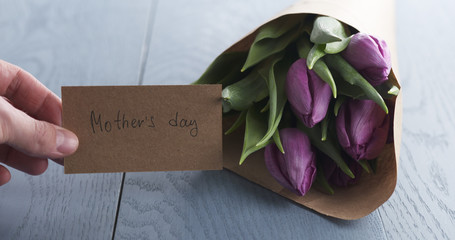 man put mothers day greeting card on blue table with bouquet of purple tulips on it, 4k photo