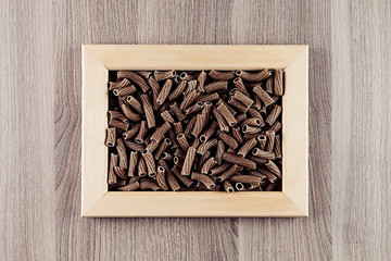 Italian dry brown twisted wholegrain pasta in wooden frame  on beige wooden board  as decorative picture background.