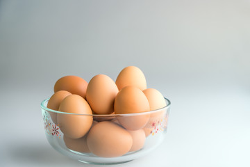Fresh eggs in a bowl on a white background.
