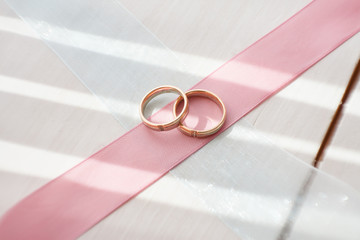 Wedding gold rings on a pink ribbon. Gold and platinum