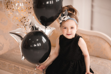 Smiling kid girl 5-6 year old holding black and silver balloons wearing stylish dress. Looking at camera. Birthday party. Childhood.