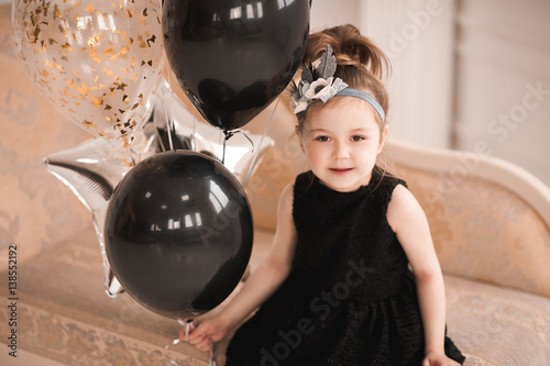 Smiling Kid Girl 5 6 Year Old Holding Black And Silver Balloons Wearing Stylish Dress Looking At Camera Birthday Party Childhood